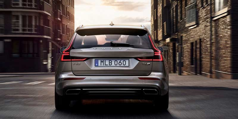 Rear view of Volvo V60 driving along narrow street