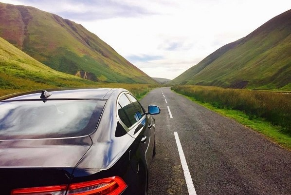 Jaguar driving on road exploring Scottish Border