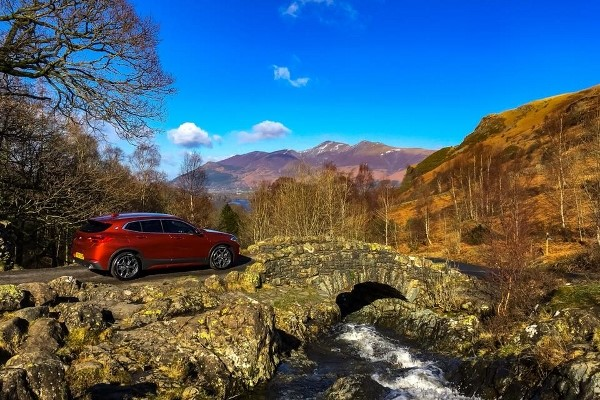 BMW exploring the Lake District parked on a bridge in sunshine